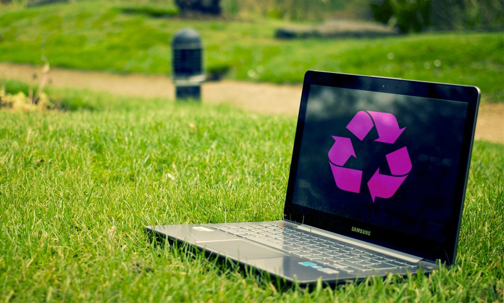 Computer on a green grass with recyling blog open